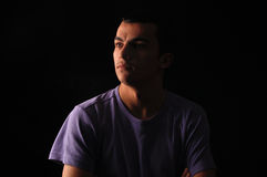 Portrait of young man wearing t-shirt standing with hands in poc Stock Image