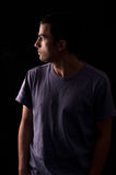Portrait of young man wearing t-shirt standing with hands in pockets. And looking on one side isolated on black background Stock Photos