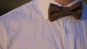 Portrait of a young man in a white shirt and a bow tie stock video