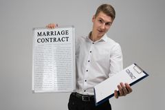 Young man holding poster with marriage contract and contract isolated on light background royalty free stock photo