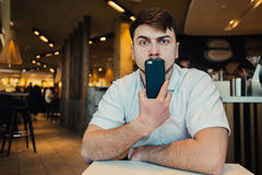 Portrait of a young man who holds the phone at the face, and puzzled looks at the camera. Portrait of a young man with a beard who keeps the phone at the face Stock Photos