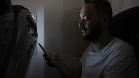 Portrait of young man, who is using his smartphone in the aircraft. Male passenger with beard and in white t-shirt is sitting on confortable chair near the stock video