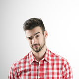 Portrait of young man winking with his right eye Royalty Free Stock Photography