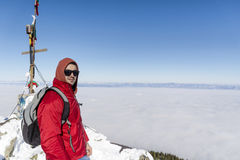 Portrait of young man in the winter mountain above the city fog Stock Images