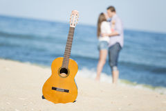 Portrait of young man and woman on a beach and guitar Royalty Free Stock Photo