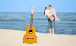 Portrait of young man and woman on a beach and guitar Royalty Free Stock Image