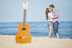 Portrait of young man and woman on a beach and guitar Royalty Free Stock Images