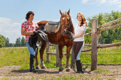 Portrait of young man and woman saddling bay horse. Portrait of young men and women saddling beautiful bay horse at sunny day in summer Stock Photo