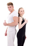 Portrait of young man and woman in sportswear thumbs up isolated Stock Images