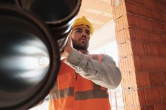Portrait Of Young Man Working In Construction Site. Proud people working in construction site. Portrait of happy white man at work in new house. Professional stock photos