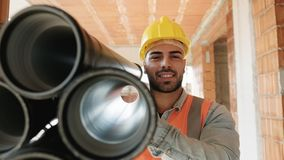Portrait Of Young Man Working In Construction Site. Proud people working in construction site. Portrait of happy white man at work in new house. Professional stock photography