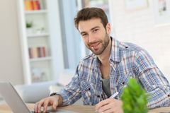 Portrait of a young man working at home on his laptop Royalty Free Stock Image