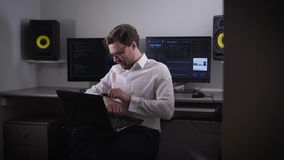 Portrait of a young man working on laptop and setting his gadget with smartwatch on his hand. Developer of contemporary stock footage