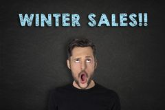 Portrait of young man with a wow expression and `Winter Sales!!!` text. Portrait of young white bearded man with a wow expression looking up to a blue `Winter stock photo