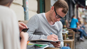 Portrait of young man writing on notebook. Royalty Free Stock Photo