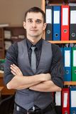 Portrait of young manager standing with crossing arms near rack with document folders Royalty Free Stock Photos