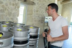 Portrait young manufacturer carrying kegs in brewery Stock Images