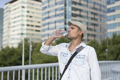Portrait of a young and masculine man drinking a water outside. Young and masculine man drinking a water outside Royalty Free Stock Photography
