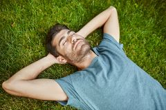 Portrait of young mature good-looking caucasian man in blue shirt peaceful lying on grass with yes closed. Guy sleeping. In garden near country house in Royalty Free Stock Image