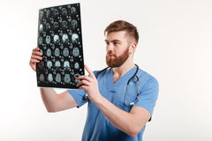 Portrait of a young medical doctor analyzing a CT scan. Isolated on white background Stock Photography