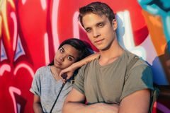 Young couple with attitude standing together by graffiti. Portrait of a young men with attitude standing with his arms crossed in front of graffiti in the city royalty free stock photography