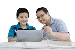 Young man guides his student to use a laptop. Portrait of young men guides his student to use a laptop, isolated on white background Royalty Free Stock Photos