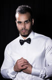 Portrait of young men. Portrait of young man in white shirt with bow tie on black background Stock Images