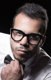 Portrait of young men. Portrait of young man in white shirt with bow tie on and glasses black background Royalty Free Stock Image