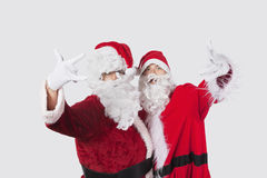 Portrait of young men in Santa costume gesturing over gray background Stock Image