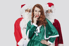 Portrait of young men in Santa costume standing with woman against gray background Royalty Free Stock Images