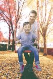 Young man pushing his son on the swing. Portrait of a young men smiling at the camera while pushing his son on the swing. Shot at autumn time Stock Photo