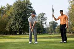 Portrait of young men standing with golf sticks on golf course stock images