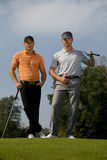 Portrait of young men standing with golf sticks on golf course Royalty Free Stock Photos