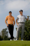 Portrait of young men standing with golf sticks on golf course Royalty Free Stock Photography