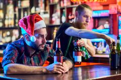 Lonely Drunk Man on Christmas. Portrait of young men wearing Santa hat getting drunk alone sitting at bar counter drinking beer at Christmas Stock Photos