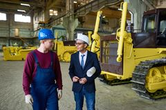 Crawlers Factory. Portrait of young Middle-Eastern engineer talking to factory worker walking across industrial workshop with tractor, copy space Royalty Free Stock Images