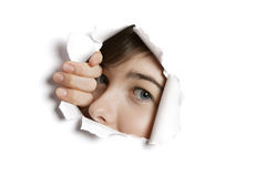 Portrait of a young Middle eastern woman peeking from ripped white paper hole Stock Photography