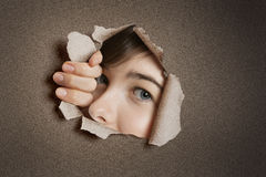 Portrait of a young Middle eastern woman peeking from ripped white paper hole Royalty Free Stock Photos