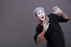 Portrait of young mime boy showing something with Royalty Free Stock Photo