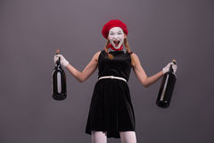 Portrait of young mime girl holding big bottles in Stock Photos