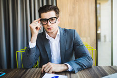Portrait of young minded man thinking about task in office Stock Photo