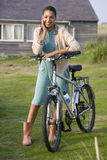 Portrait of young mixed race woman with bicycle outdoors Stock Photography