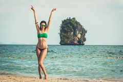 Young model woman, raising her arms Railay beach, popular travel destination near Krabi, Thailand. royalty free stock image