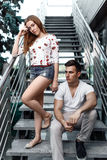Portrait of young modern couple in love, posing outdoors in city street Stock Photos