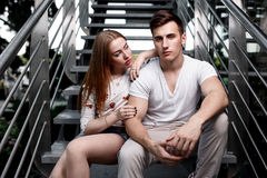 Portrait of young modern couple in love, posing outdoors in city street Stock Photo