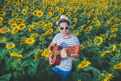 Guitar player in sunflower field Royalty Free Stock Photography