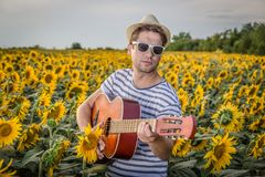 Guitar player in sunflower field Stock Photo