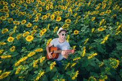 Guitar player in sunflower field Stock Image