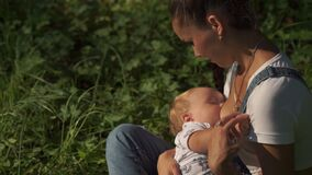 Portrait of young mother breastfeeding son in the park. Emotional scene of toddler drinking mom breast surrounded by