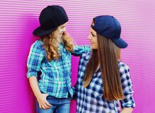 Portrait of young mother with child little girl wearing a checkered shirts and baseball cap in city over pink